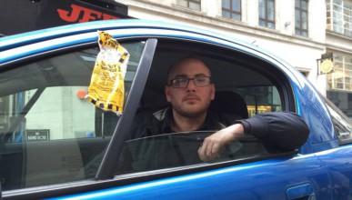 Мъж стоя в колата си, докато паяк я вдигаше